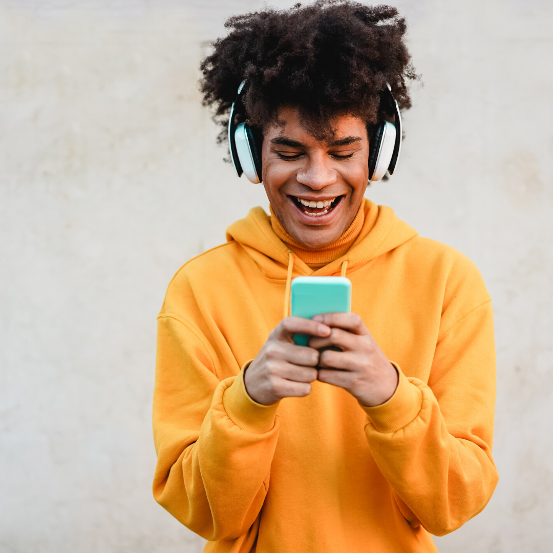 Jongen met koptelefoon kijkt naar smartphone