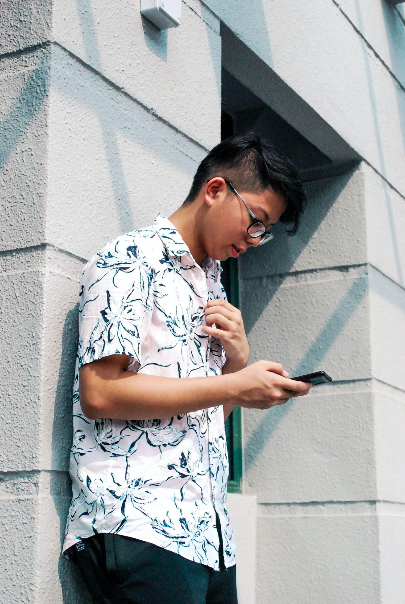Jongen leunt tegen muur en kijkt naar smartphone